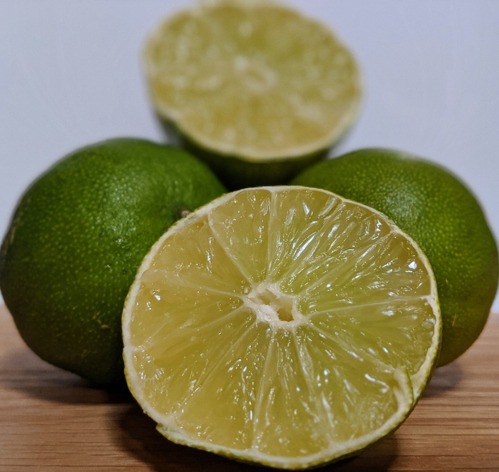Bright green limes gathered together with one lime cut in half to show juicy center.