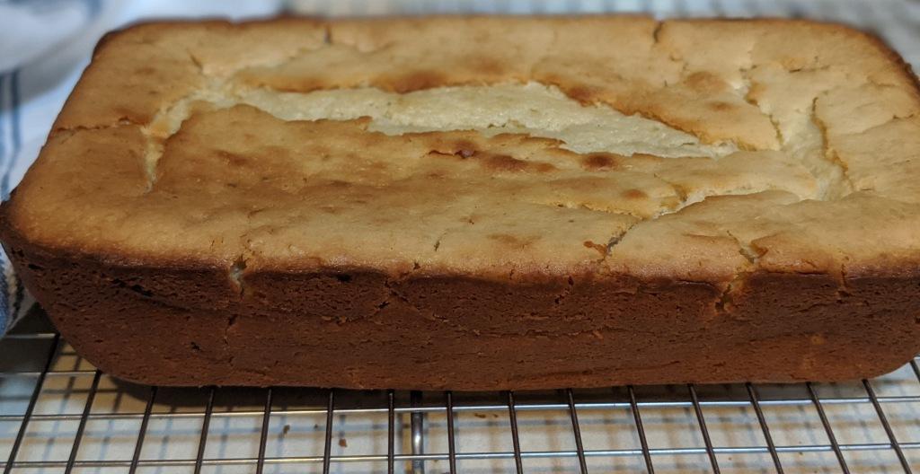Golden brown loaf cake cooling on wire rack.