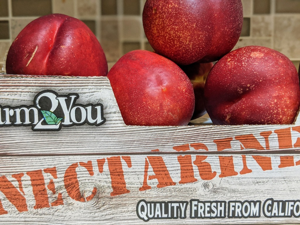 A juicy, plump pile of fresh nectarines in a crate.