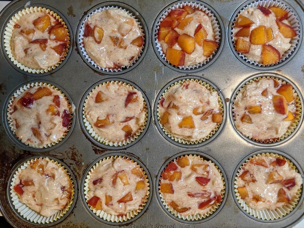 Cupcake tray, lined with 12 filled cups. Nectarine compote is peaking out and bursting with color and soon to be flavor.