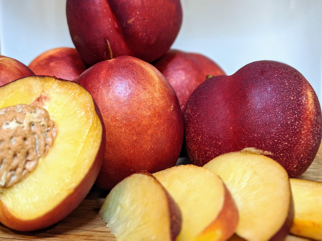 Pile of ripe nectarines, one sliced open showing the soft, yellow center. Slices of nectarine to the side
