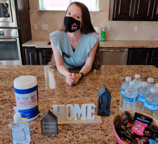 Albuquerque Real Estate agent, Elizabeth Benedict, posing in a kitchen during an open house alongside disinfectant to demonstrate best practices during open houses