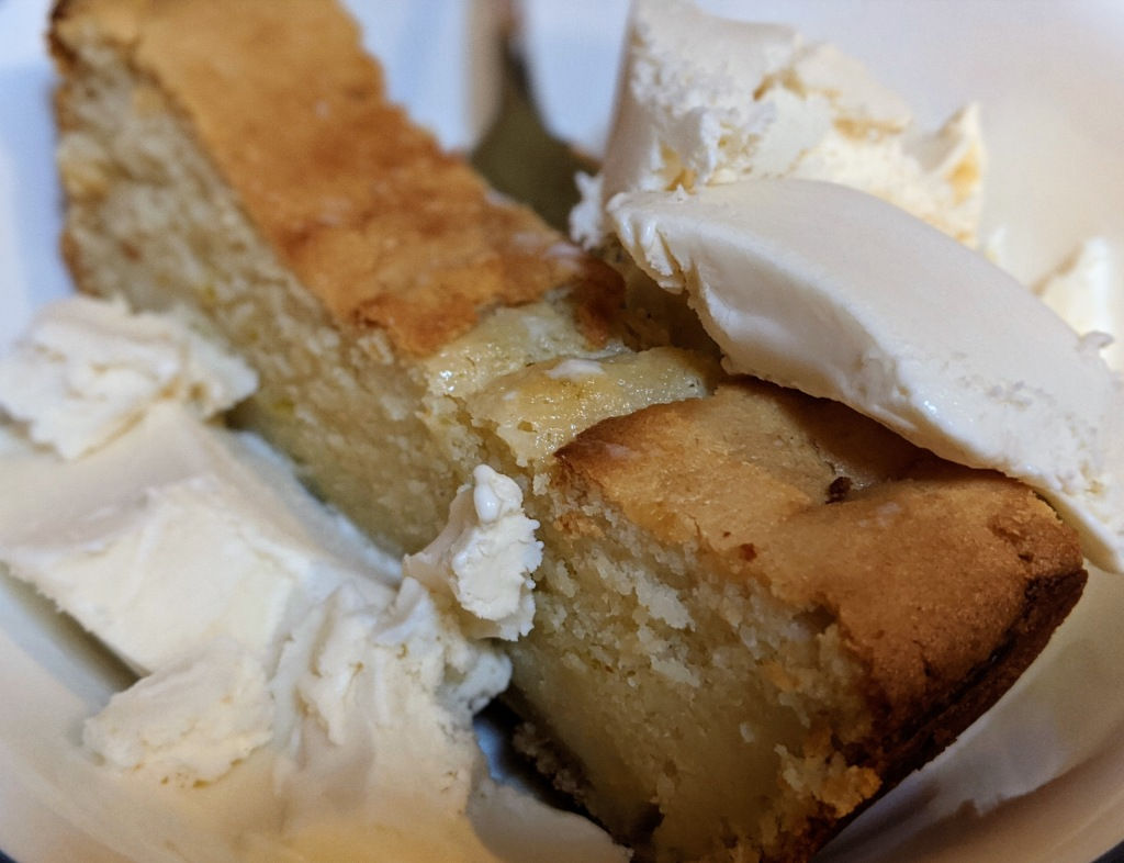 A slice of golden delicious cake with two heaping scoops of vanilla ice cream surrounding it.