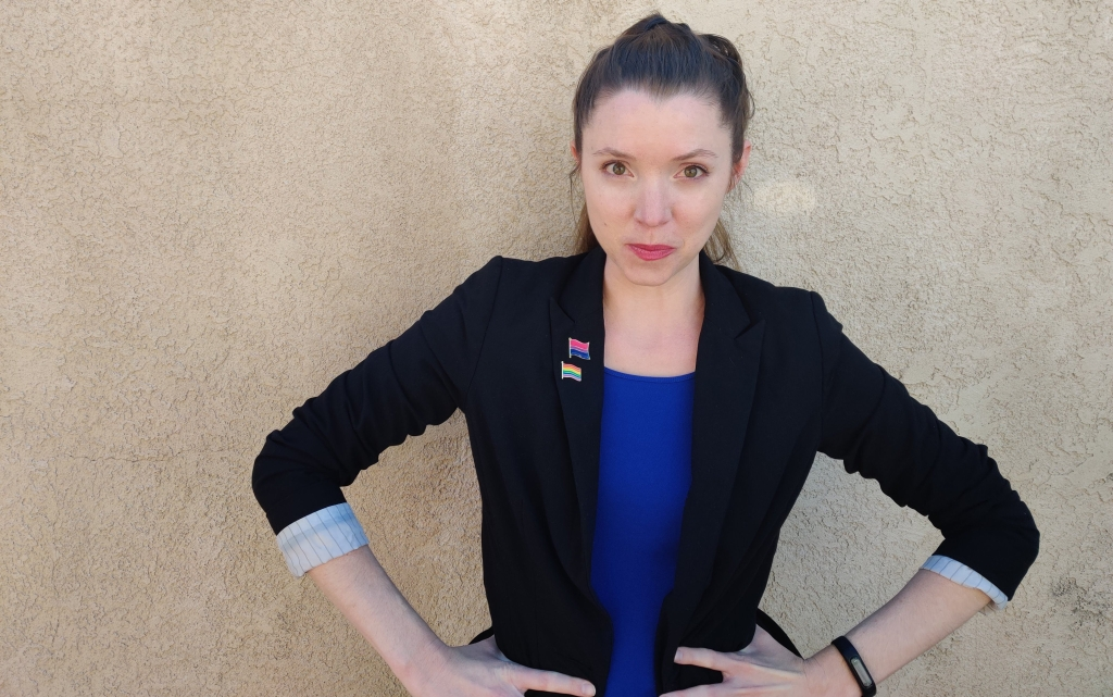 Albuquerque Real Estate Agent, Elizabeth Benedict, standing in front of an adobe wall with a determined look representing her commitment to Fair and Equal Housing