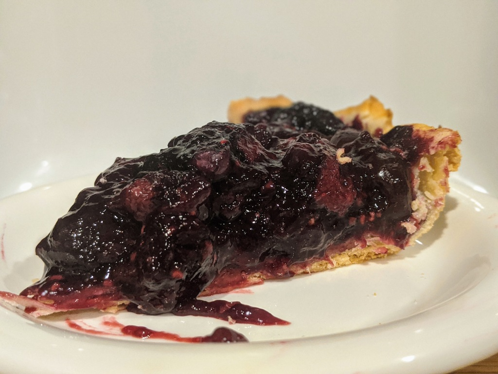 Slice of cherry berry pie, with a golden buttery crust ready to be devoured.