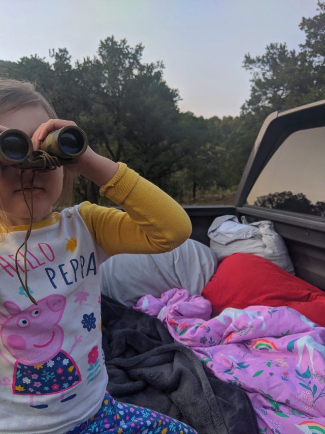 My three year old sitting in a truck bed and looking through binoculars