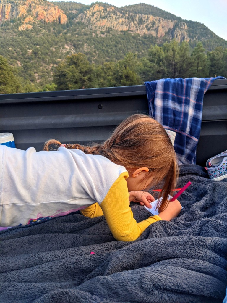Three year old resting on elbows and drawing in truck bed with mountains in the background