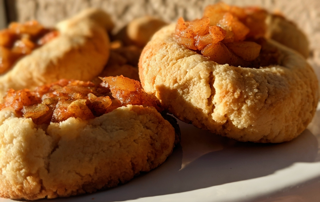 Cookies filled with apple pie filling jam basking in the sunlight. The light makes both the cookie and filling have a golden glow