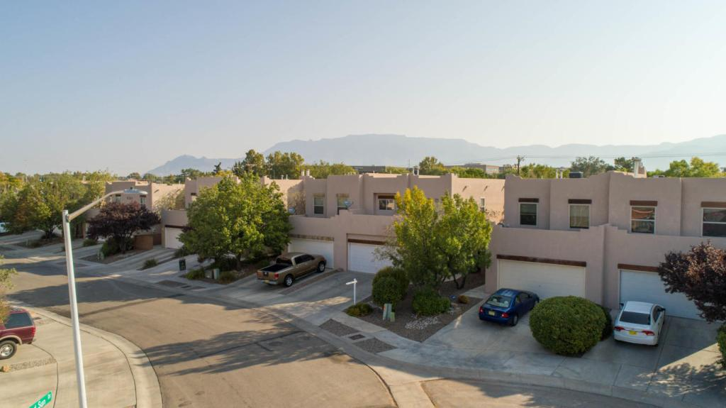 Drone shot of the exterior of the townhome with the Sandia Mountains in the background