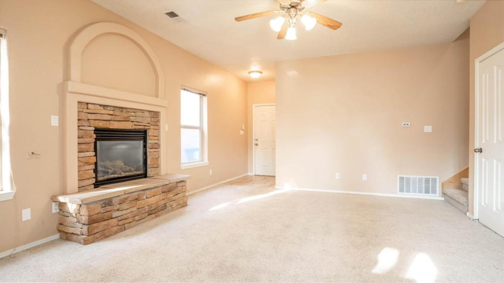 Interior shot of the living and family room with a stone fireplace focal point. Beighe carpet and tan walls.