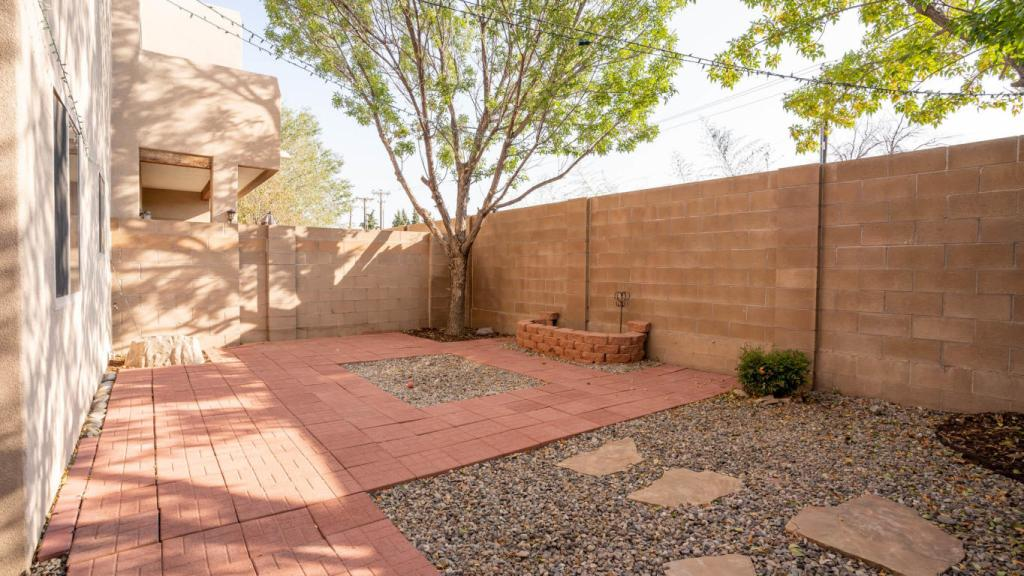 Exterior shot of the patio with brick pavers, string lights, and green trees.