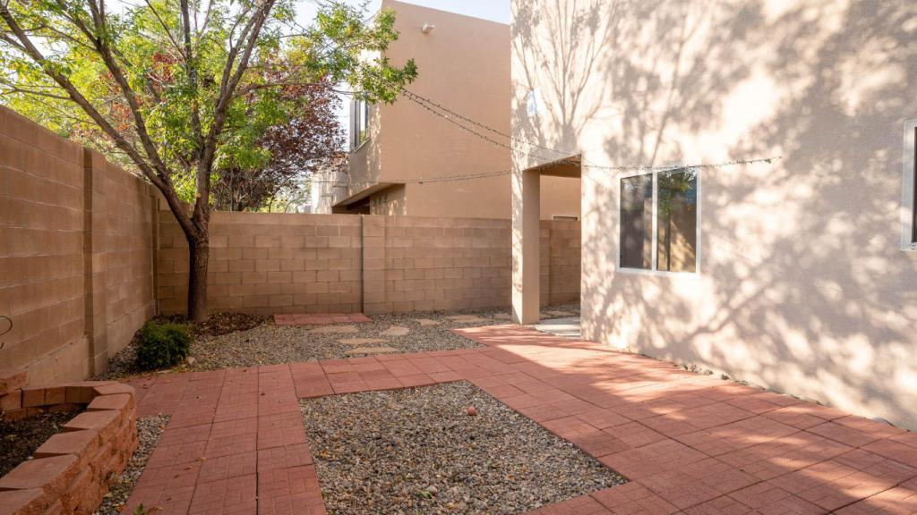 Exterior shot of the backyard with view of covered patio, brick pavers, raised beds, and green tree in corner.