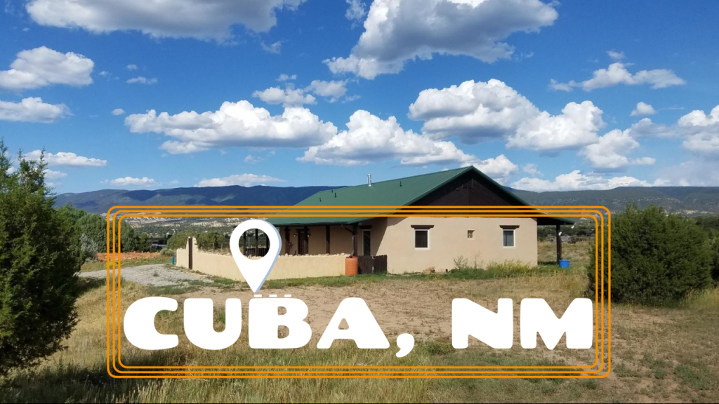 Landscape picture of a Northern New Mexico sytle ranch in Cuba New Mexico. Bright blue skies and fluffy white clouds and surrounding mountain terrain.