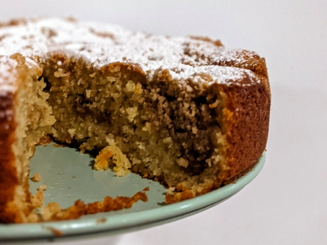 Side view of creumb cake topped with powdered sugar. Slice is cut out, inside you see the crumble inside and out.
